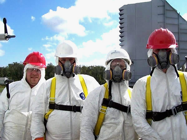 Four men in safety gear and respirators ready to treat a bird problem in a power plant